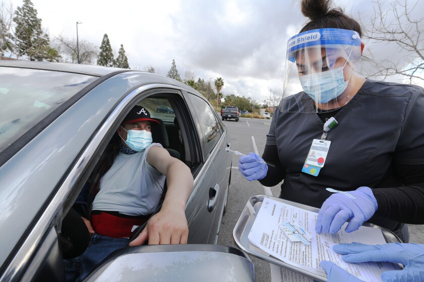A man waits in a car with his sleeve rolled up as a woman holds a syringe.