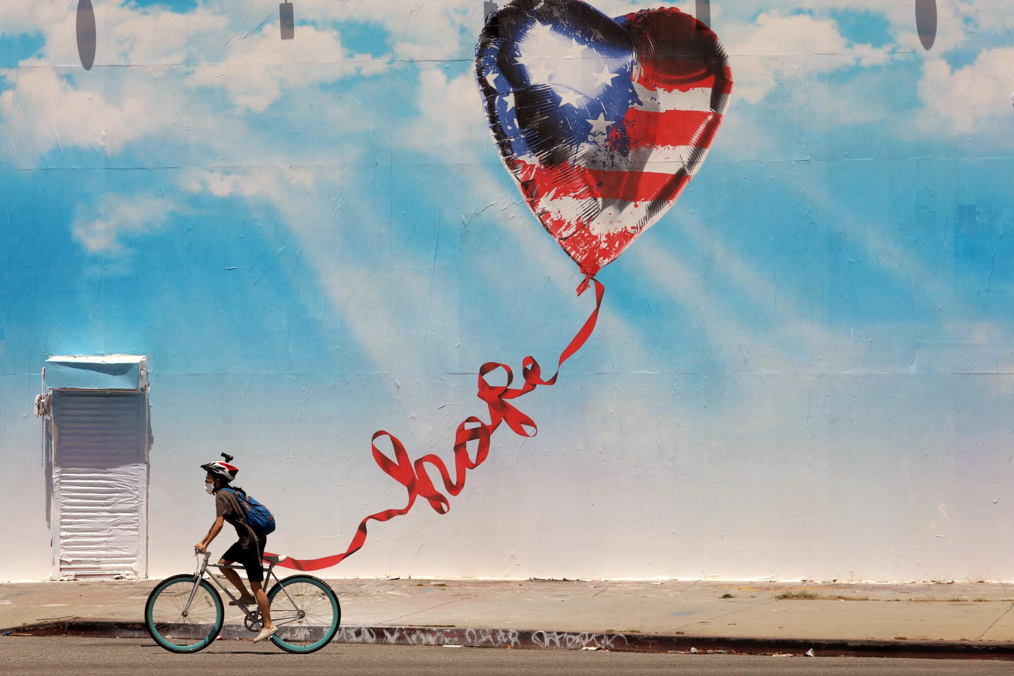 A bicyclist rides past a mural in Los Angeles.