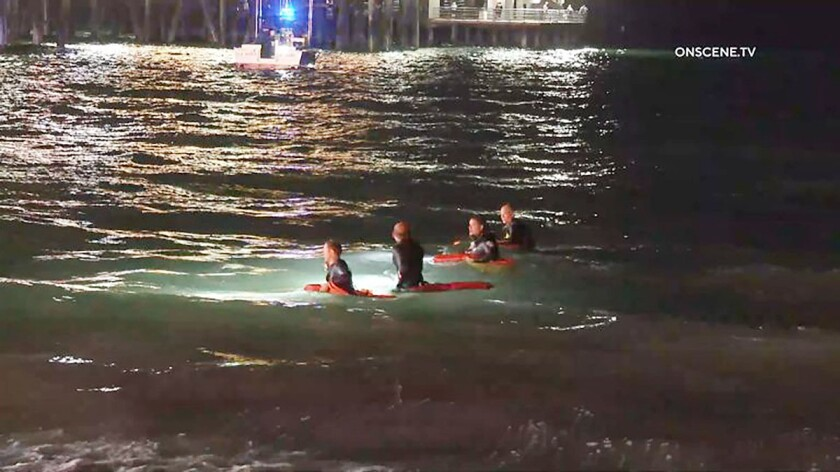 Lifeguards search the water near the Santa Monica Pier at night.