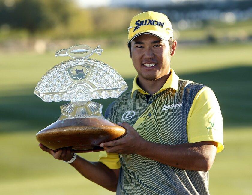 Hideki Matsuyama holds the trophy after winning the Phoenix Open golf tournament, Sunday, Feb. 7, 2016, in Scottsdale, Ariz. (AP Photo/Rick Scuteri)