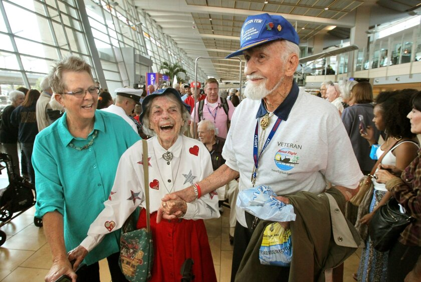 World War II Marine veteran Victor Freudenberger, 95, of Carlsbad, walks with wife Skippy, 99, and their daughter Laurie Carlisle as he returns from Washington D.C. with other veterans on Honor Flight San Diego.