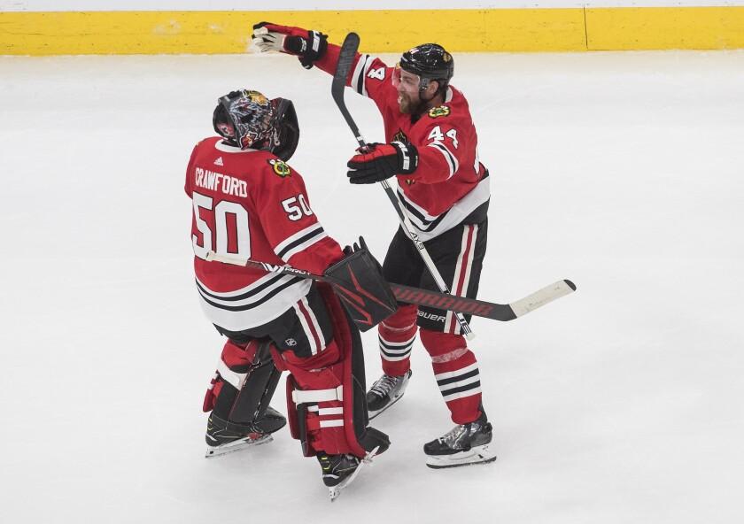 Chicago Blackhawks goalie Corey Crawford (50) and Calvin de Haan (44) celebrate their win over the Edmonton Oilers in an NHL hockey playoff game Friday, Aug. 7, 2020, in Edmonton, Alberta. (Jason Franson/Canadian Press via AP)