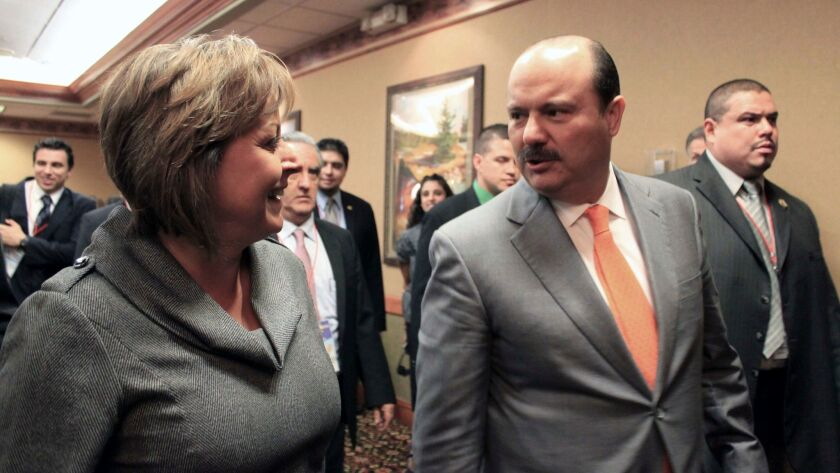 New Mexico Gov. Susana Martinez, left, and Cesar Duarte talk in Albuquerque in 2012. Mexico's federal officials will take over an investigation into Duarte, who is accused of diverting public funds.