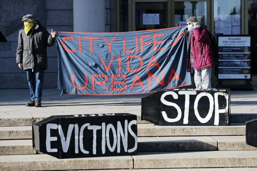 """People in masks and winter coats stand on the steps of a building with signs that read """"Stop Evictions"""" and """"City Life."""""""