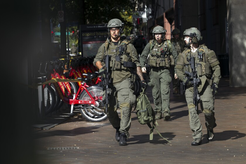 Montgomery County police officers in tactical gear exit a parking garage where a police officer was shot, in downtown Silver Spring, Md., Monday, Oct. 14, 2019. Police in Montgomery County, Maryland, said they were searching for at least one person after an officer was found shot in a parking garage in downtown Silver Spring on Monday. (AP Photo/Jose Luis Magana)