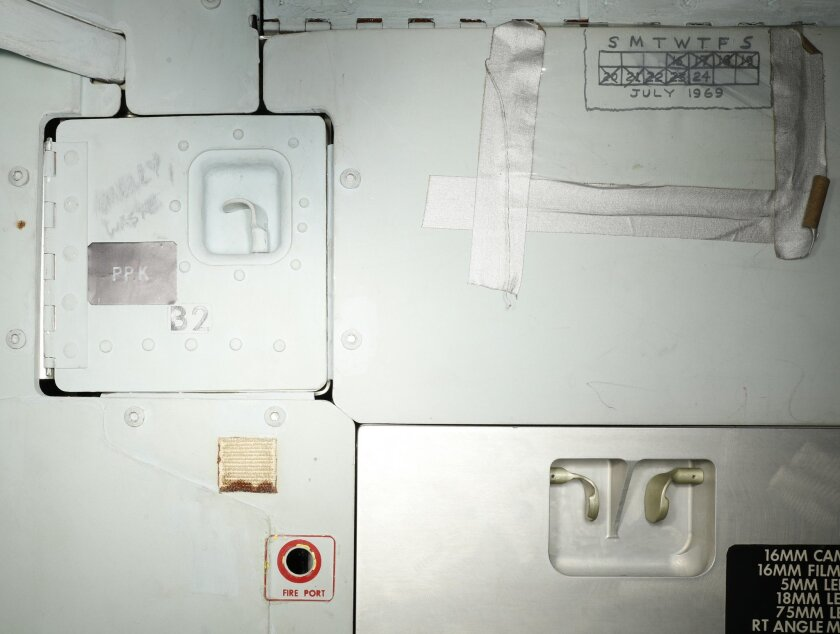This image provided by the Smithsonian Institution shows part of the interior of the Apollo 11 command module that shows graffiti left by astronauts Neil Armstrong, Buzz Aldrin and Michael Collins. A calendar hand drawn on the wall marking days in space and scribbled warning instructions to not ope