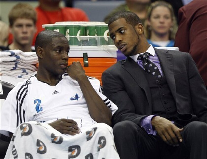 New Orleans Hornets guard Darren Collison (2) sits with Hornets starting guard Chris Paul during the first half of an NBA basketball game against the Phoenix Suns in New Orleans, Monday, Feb. 1, 2010. Paul injured his knee during a game Wednesday, reinjured it Friday, and is out indefinitely. (AP Photo/Patrick Semansky)