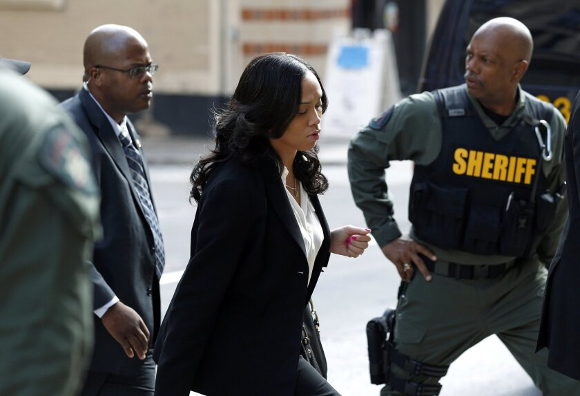 Baltimore state's attorney Marilyn Mosby, center, arrives at a courthouse before opening statements in the trial of Lt. Brian Rice, one of six members of the Baltimore Police Department charged in connection to the death of Freddie Gray, in Baltimore, Thursday, July 7, 2016. (AP Photo/Patrick Seman