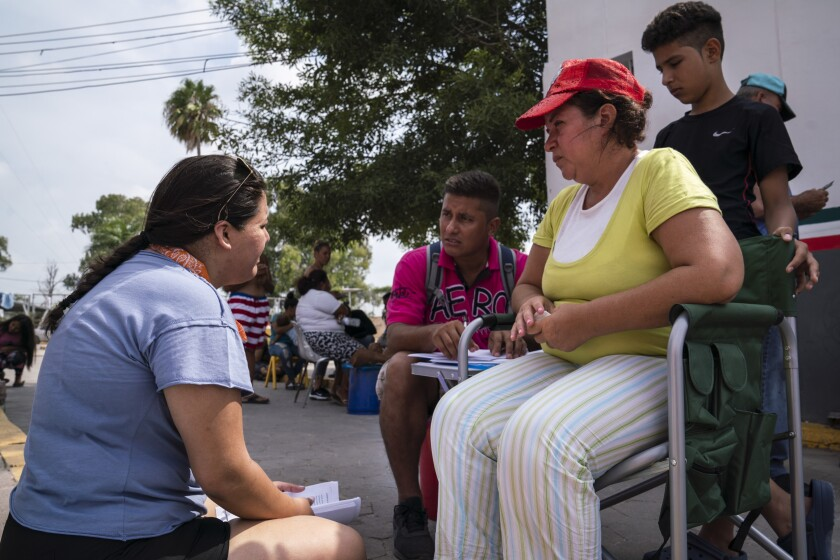 """Volunteer lawyer Joan Orejuela, left, listens to asylum seekers William Erazo Antunez, 36, wife Claudia Oliva Garcia, 42, and their son William at a workshop on asylum claims on Aug. 24, 2019. The family was sent to Matamoros to wait for their asylum claim in Mexico under the Trump administration's """"Remain in Mexico"""" policy."""