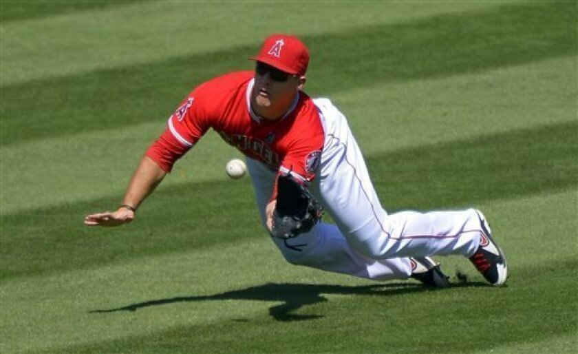 Los Angeles Angels center fielder Mike Trout makes a diving catch on a ball hit by Seattle Mariners' Carlos Triunfel during the third inning of a baseball game on Sunday, Sept. 22, 2013, in Anaheim, Calif. (AP Photo/Mark J. Terrill)