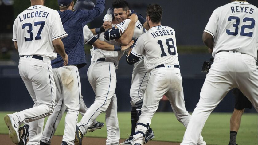 The Padres celebrate after a walk-off single by Christian Villanueva (center right) on Saturday against the Diamondbacks.
