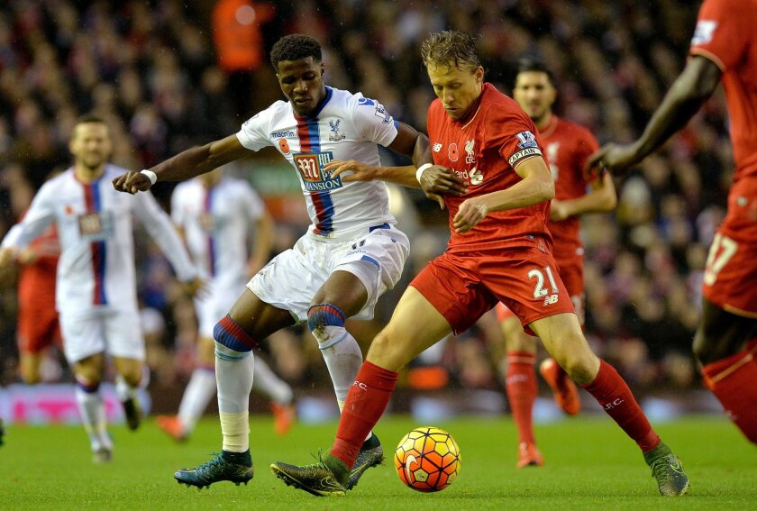 Crystal Palace's Wilfried Zaha, left, battles for the ball with Liverpool's Lucas Leiva during the English Premier League soccer match at Anfield, Liverpool, England, Sunday Nov. 8, 2015. (Martin Rickett/PA via AP) UNITED KINGDOM OUT