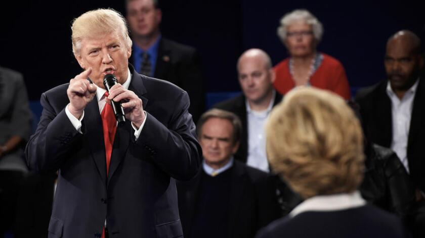 Donald Trump habla con Hillary Clinton durante el segundo debate.