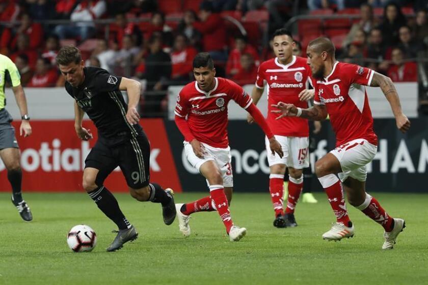 El jugador Kriztian Nemeth (i) del Sporting Kansas City disputa la pelota con Iván Acero (c) de Toluca, este jueves, durante el juego correspondiente a los octavos de final de la liga de Campeones de la CONCACAF, en el estadio Nemesio Diez, en la ciudad de Toluca (México). EFE
