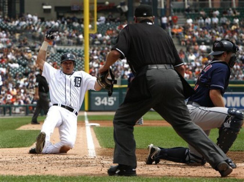 Detroit Tigers' Magglio Ordonez slides into home plate safely as umpire Jim Joyce looks on against the Cleveland Indians during the third inning of a baseball game in Detroit Thursday, June 3, 2010. (AP Photo/Paul Sancya)