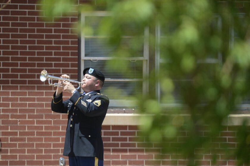 Staff Sgt. Luis Ortiz plays taps at Provider's Chapel at Fort Carson, Colo. Tuesday, June 10, 2014, during a memorial service for Pfc. Jacob H. Wykstra. Wykstra died last month in a helicopter crash in Afghanistan. (AP Photo/The Gazette, Mark Reis)