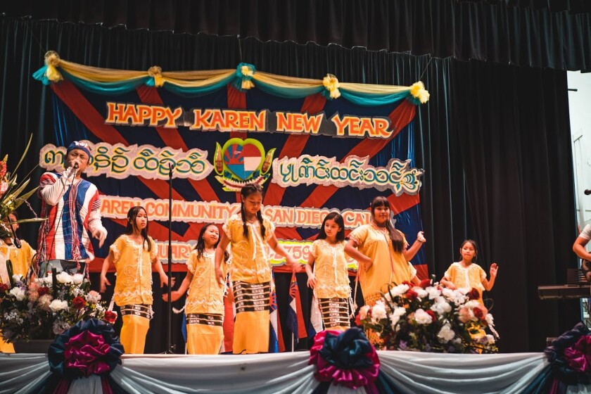 "Young dancers hold hands on stage in front of a sign that reads ""Happy Karen New Year"""