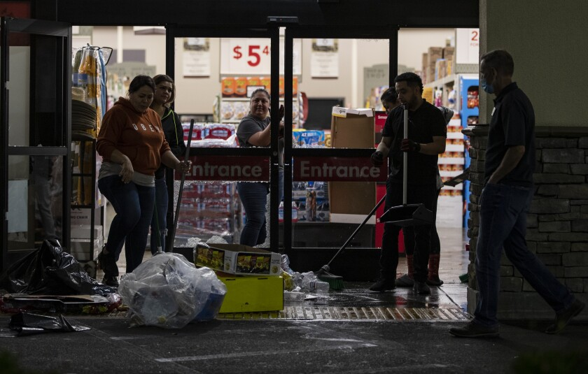 Workers at the Smart & Final store clean up debris and damage caused by looters