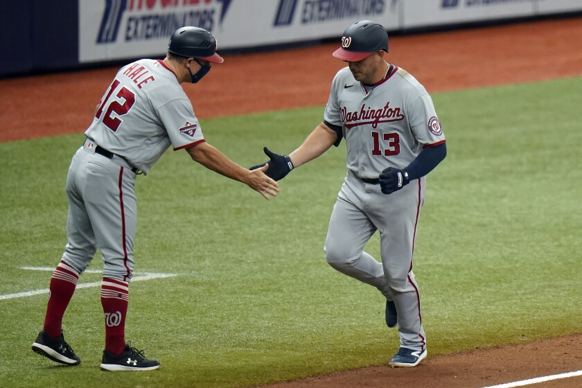 Washington Nationals' Asdrubal Cabrera (13) shakes hands with third base coach Chip Hale (12) after Cabrera hit a two-run home run off Tampa Bay Rays pitcher Oliver Drake during the sixth inning of a baseball game Wednesday, Sept. 16, 2020, in St. Petersburg, Fla. (AP Photo/Chris O'Meara)