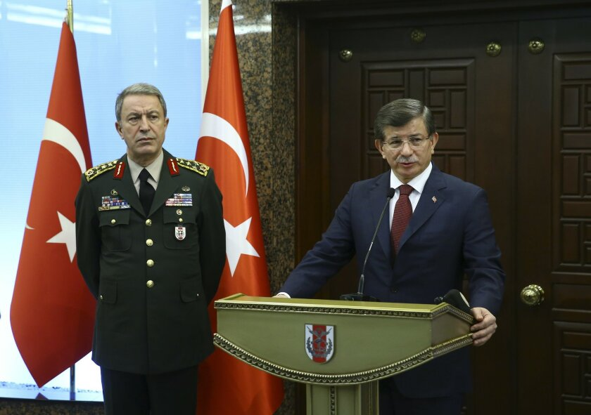 Turkish Prime Minister Ahmet Davutoglu, right, accompanied by Turkish Forces' Chief of Staff Gen. Hulusi Akar, makes a statement regarding Wednesday's explosion in Ankara, Turkey, following their meeting, Thursday, Feb. 18, 2016. The explosion occurred during evening rush hour in the heart of Ankar