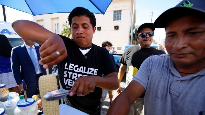 Benjamin Ramirez, left, with his father, Alex Ramirez, right, serving food from their cart during a rally in Hollywood.