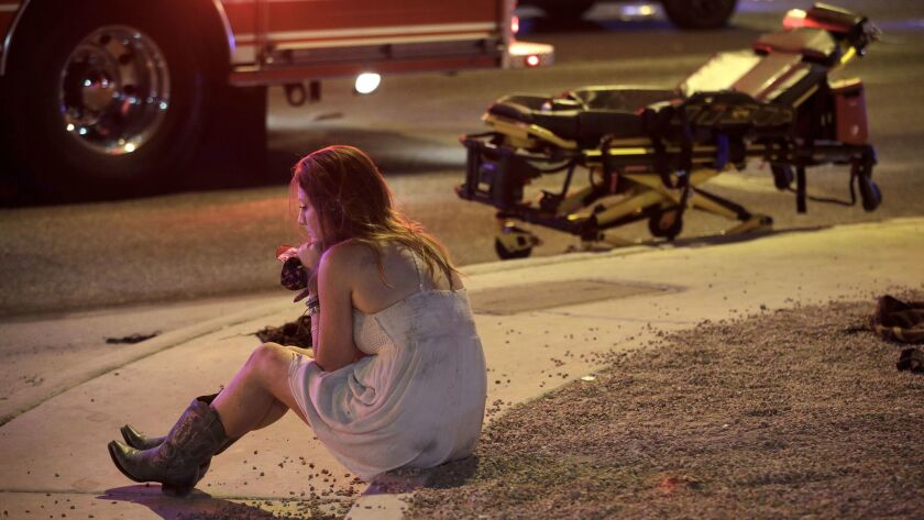 A woman sits on a curb at the scene of a shooting outside of a music festival along the Las Vegas St