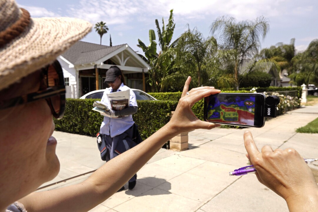 Edith de Guzman uses a smartphone to take a thermal image