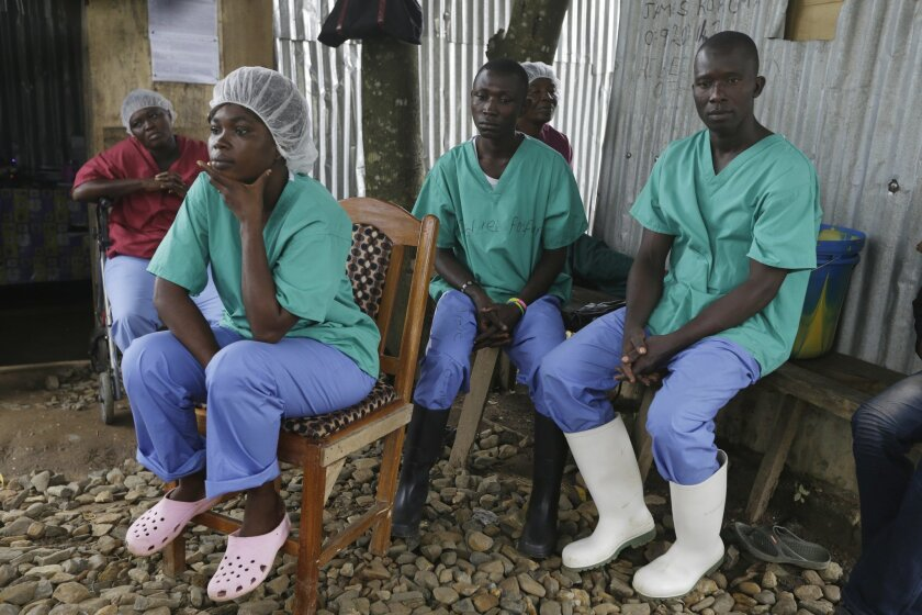 In this Monday, Aug. 10, 2015 photo, health workers take a break at the Kenema Government Hospital, where more than 40 health workers died of Ebola, in Kenema, eastern Sierra Leone. An Associated Press investigation has found a toxic mix of avoidable problems faced by Ebola responders, including weak leadership, shoddy supplies and infighting, exacerbated a chaotic situation at a critical front in the battle against the virus. (AP Photo/Sunday Alamba)
