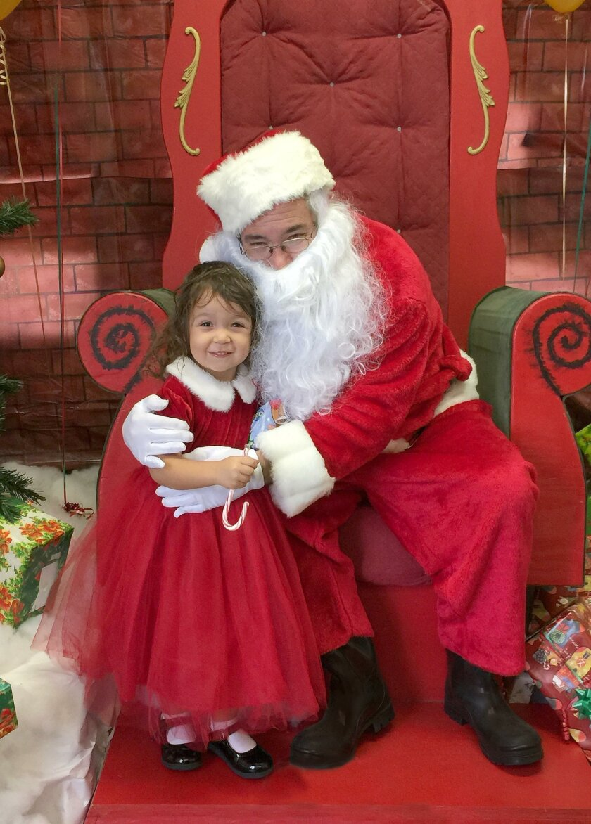 Chloe Fitzcluster gets a hug from jolly-old Saint Nick during the La Jolla Recreation Center's annual lunch with Santa Claus, Dec. 19, 2015.