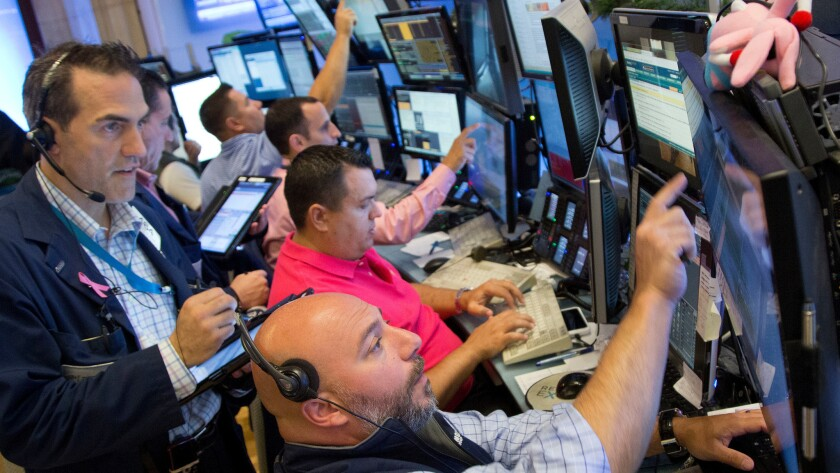 Greg Rowe, left, and Vincent Napolitano, bottom, with Livermore Trading Group monitor stock prices at the New York Stock Exchange on Friday.