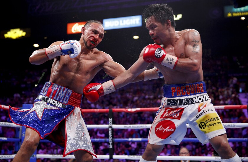 Keith Thurman, left, and Manny Pacquiao exchange punches in the eighth round during a welterweight title fight on Saturday in Las Vegas.