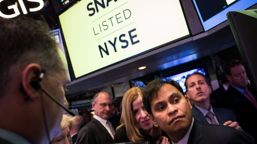 Imran Khan, right, then chief strategy officer of Snap Inc., waits for shares to open for trading on the floor of the New York Stock Exchange on March 2, 2017.