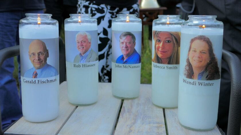Candles memorializing Gerald Fischman, Rob Hiassen, John McNamara, Rebecca Smith and Wendi Winters flicker during a candlelight vigil on June 29, 2018 in Annapolis, Md.