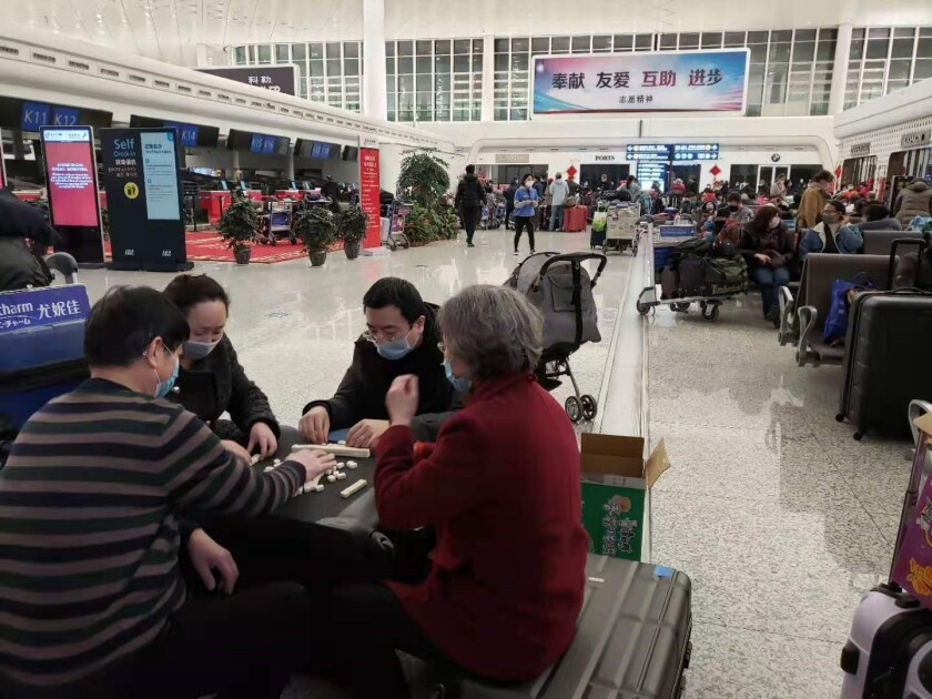 Hundreds of people waited for hours on Tuesday, Feb. 4, 2020 at Wuhan Tianhe International Airport for evacuation flights to their home countries amid an outbreak of coronavirus that has killed more than 420 people and sickened more than 20,000. A group at the airport (center left) plays mahjong while waiting to flee the Chinese city.