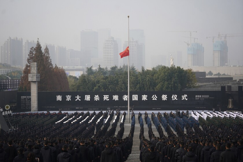 In this photo released by Xinhua News Agency, the Chinese national flag is flown at half mast during a memorial ceremony for the Nanjing Massacre victims at the Memorial Hall of the Victims of the Nanjing Massacre by Japanese Invaders in Nanjing, in eastern China's Jiangsu Province on Sunday, Dec. 13, 2020. (Ji Chunpeng/Xinhua via AP)