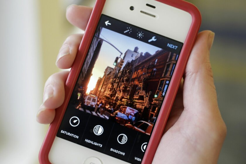 This Monday, June 9, 2014 photo shows the Instagram app, featuring new editing tools, on an iPhone posed for a photo in New York. Instagram, available for iOS 6.0 and later and Android phones, recently introduced 10 new editing tools. (AP Photo/Mark Lennihan)