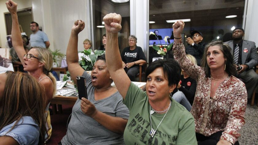 """Amie Zamudio, left, Tasha Williamson, second from left, Maria Little, second from right, and Aaryn Belfer, right, raise their fists as they chant """"Who killed Earl McNeil"""" while they watch a meeting on a television monitor outside of the council chambers Tuesday in National City."""