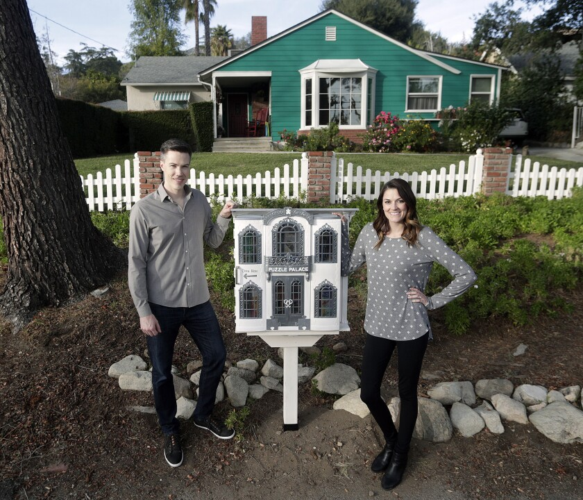 Luke and Jessica Cheney with a homemade puzzle trading post they made from a Barbie Grand Hotel and installed at Jessica's parents' Mountain Avenue home in La Crescenta.