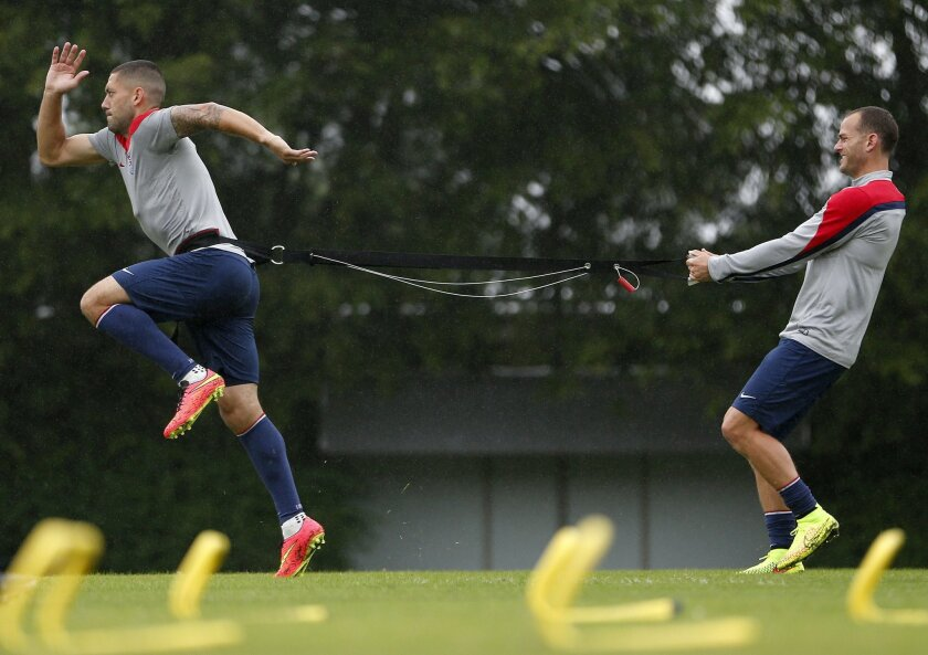 United States' Clint Dempsey, left, and Brad Davis work on resistance exercises during a training session at the Sao Paulo FC training center in Sao Paulo, Brazil, Tuesday, June 10, 2014. The U.S. will play in group G of the 2014 soccer World Cup. (AP Photo/Julio Cortez)