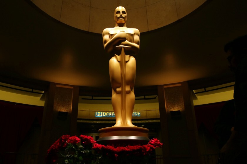 A giant Oscars statue stands in a lobby with flowers laid at its base