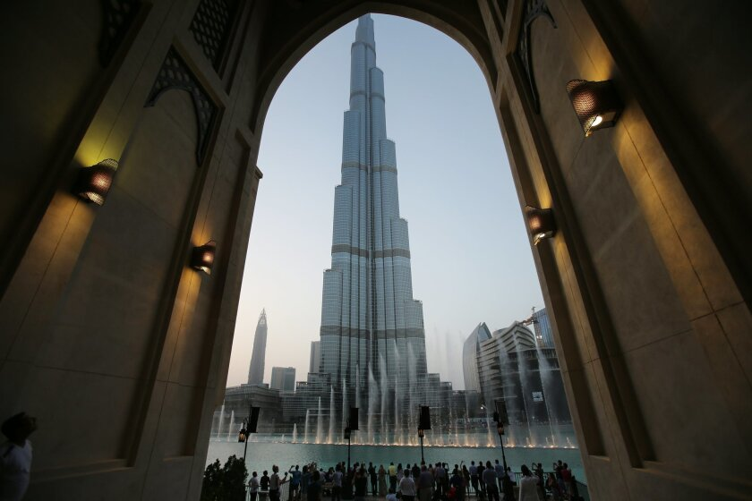 FILE - In this Monday, April 13, 2015, with the world tallest tower, Burj Khalifa, in the background, tourists and visitors watch and take photos of the Dubai Fountain in Dubai, United Arab Emirates. The Burj Khalifa announced Thursday, Nov. 5, it is selling tickets on the United Arab Emirates' wee