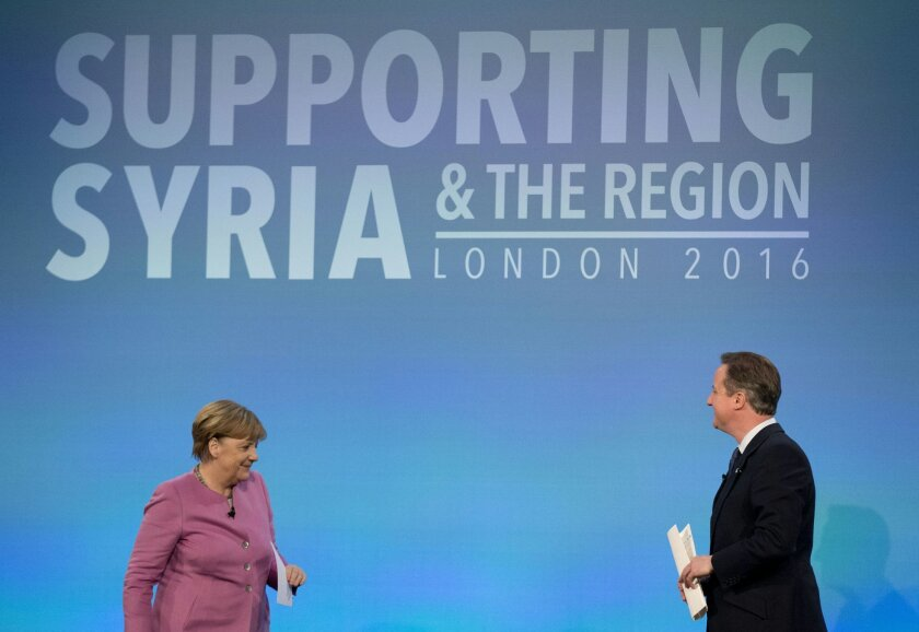 FILE - In this file photo dated Thursday, Feb. 4, 2016, British Prime Minister David Cameron, right, walks back to his seat on the stage after speaking, as German Chancellor Angela Merkel gets up for her turn to speak during a press conference near the end of the 'Supporting Syria and the Region' c