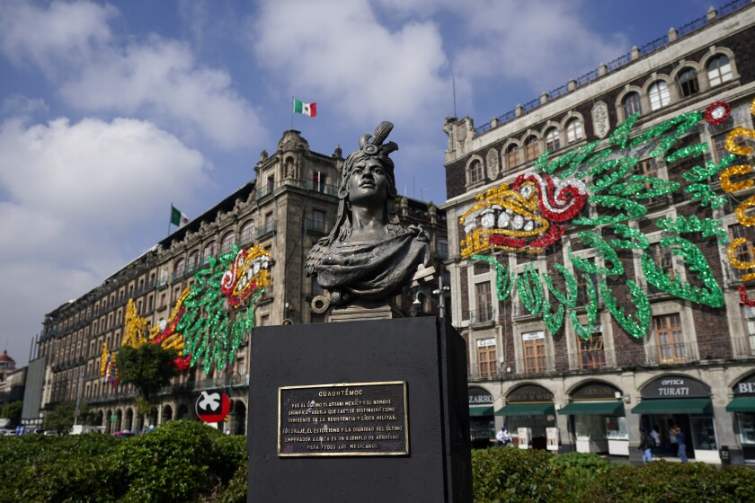 A bust of Aztec emperor Cuauhtemoc in Mexico City's main square with images of Aztec god Quetzalcoatl on nearby buildings.