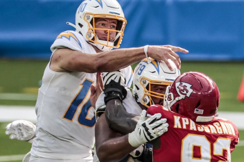 Chargers quarterback Justin Herbert passes under pressure.