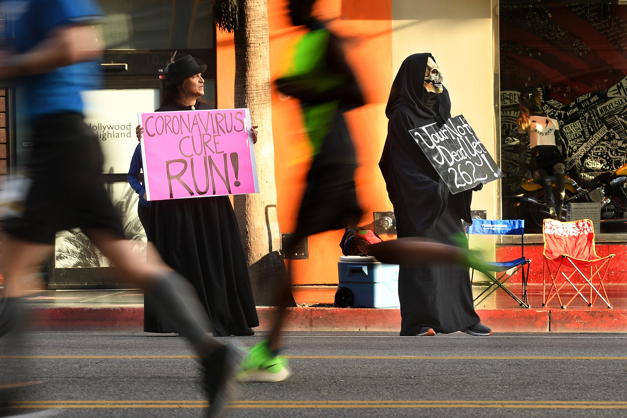 Janette Cardona and her husband, Louie, hold signs along Hollywood Blvd. as runners compete during L.A. Marathon.