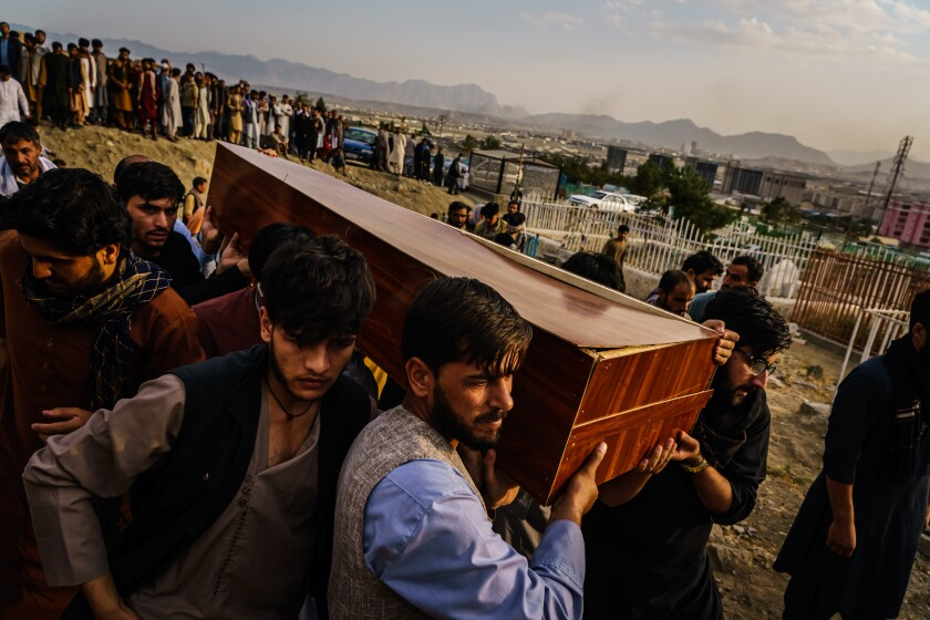 Caskets are carried toward a gravesite during a mass funeral for members of a family killed in an airstrike in Afghanistan.