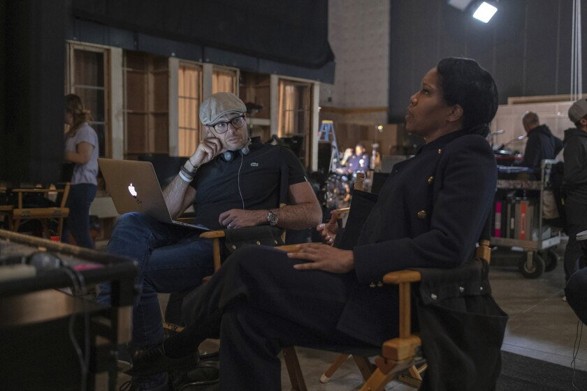"Damon Lindelof and Regina King on the set of HBO's ""Watchmen."""