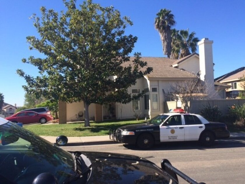 Police cars are parked in front of a Carmel Mountain house where residents were victims of a home invasion robbery.