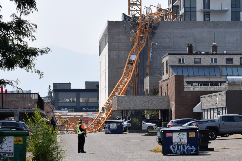 A worker looks on as a police officer investigates a collapsed crane resting on the building it damaged in Kelowna, Brith Columbia, Monday, July 12, 2021. Five people died when a crane toppled off a 25-story residential tower in Canada, police said Tuesday. (Alistair Waters/The Canadian Press via AP)