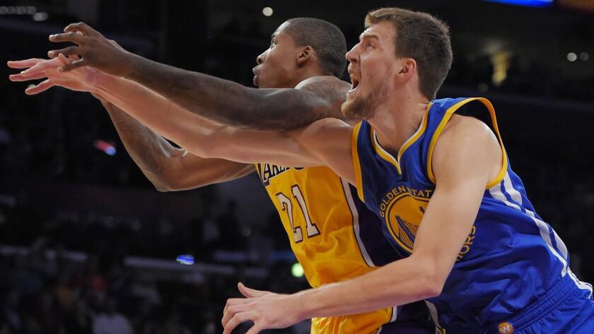 Lakers forward Ed Davis, left, battles Golden State Warriors center Ognjen Kuzmic for a loose ball during a preseason game on Oct. 9.